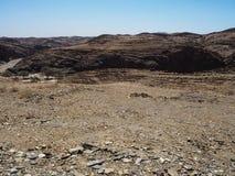纳米比亚沙漠独特的地理自然岩石山纹理风景背景与分裂的石含沙地面,沙漠树的 图库摄影