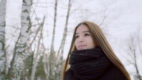 纵向冬天妇女年轻人 没有头饰的一个女孩通过冬天公园走 股票视频