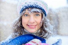 纵向冬天妇女年轻人 笑秀丽欢悦式样的女孩接触她的面孔皮肤和,获得乐趣在冬天公园 义卖市场 免版税库存图片