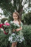 纵向微笑的美丽少年与雏菊花束,夏天公园绿色 库存图片