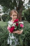 纵向微笑的美丽少年与雏菊花束,夏天公园绿色 免版税库存照片