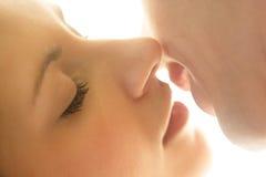 纵向新白种人夫妇亲吻 免版税库存图片