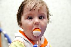 纵向有玩具球的男婴在嘴 库存照片
