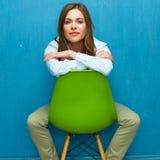 纵向认为的妇女 女孩坐绿色椅子 免版税图库摄影