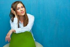 纵向认为的妇女 女孩坐绿色椅子 免版税库存照片