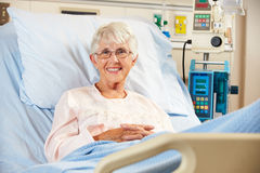 纵向高级女性耐心放松在医院病床上 图库摄影