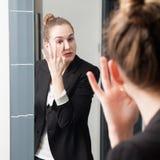 纵容应用在镜子的美丽的年轻聪明的妇女眼睛concealer 库存图片