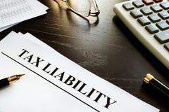 纸以标题在书桌上的纳税义务 免版税库存照片
