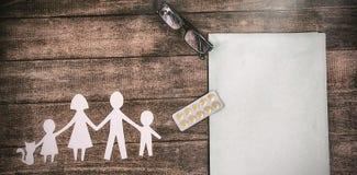 纸删去了与医学的家庭在桌上的链子和文件 图库摄影