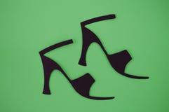 纸删去了在绿色背景的妇女的凉鞋 免版税库存图片