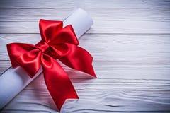 纸卷与红色弓的在木板假日概念 库存图片