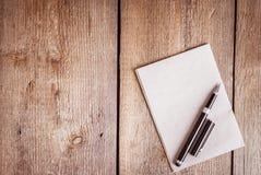 纸和笔在木背景 免版税库存照片