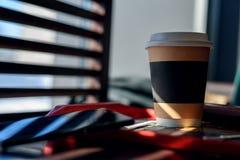 纸和纸板杯用咖啡,热奶咖啡,拿铁,在一张木桌上的茶在咖啡馆在明亮的阳光下从在Th的窗口 免版税库存照片