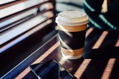 纸和纸板杯用咖啡,热奶咖啡,拿铁,在一张木桌上的茶在咖啡馆在明亮的阳光下从在Th的窗口 库存图片