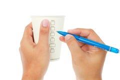 纸咖啡在白色的和检查菜单 库存图片