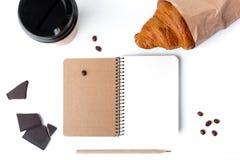 纸咖啡杯、新月形面包、巧克力、在白色背景隔绝的笔记本和pancil 免版税库存照片