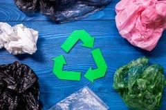 纸回收与塑料垃圾的标志在蓝色木背景顶视图 库存图片
