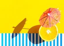 纸在明亮的黄色蓝色和白色镶边背景的饮料伞新鲜的水多的桔子 苛刻的轻的坚硬阴影 ?? 库存照片