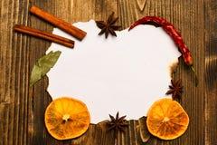 纸在木背景的 香料,厨房草本在白皮书附近放置 肉桂条,干桔子和 免版税图库摄影