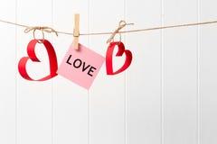 纸垂悬在白色背景的线的心脏和爱 免版税库存照片