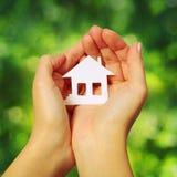纸家庭和心脏移交绿色晴朗的背景 图库摄影