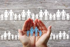 纸家庭在木背景的手上与白色家庭 免版税图库摄影