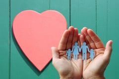 纸家庭在木背景的手上与红色心脏 免版税库存照片