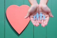 纸家庭在木背景的手上与红色心脏 库存照片