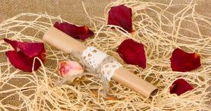 纸封皮在西沙尔麻说谎 在干燥玫瑰花瓣背景的纸卷  库存图片
