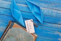纸小船与葡萄酒书和标志生活是冒险-旅行概念 库存图片