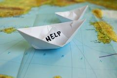 纸小船地图帮助难民 库存图片