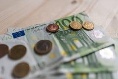纸币票据和欧洲硬币在桌上 免版税库存图片