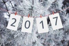 纸或照片框架与垂悬在红色镶边绳索的2017年 一棵多雪的杉木的照片在背景的 设计新年度 免版税库存照片