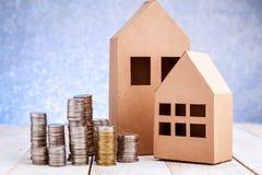 纸房子和堆硬币站立 免版税库存图片