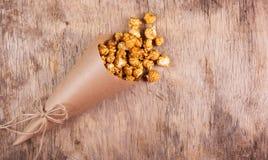 纸杯用在木背景的焦糖玉米花 图库摄影