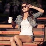 从纸杯的少妇饮用的咖啡 坐长凳 图库摄影