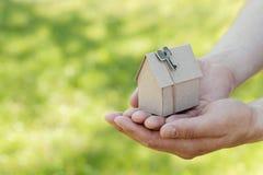 纸板房子男性手举行反对绿色bokeh的 大厦、贷款、乔迁庆宴、保险、房地产或者购买新的家 库存照片