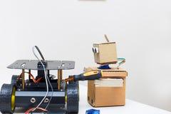 纸板机器人拿着一个螺丝刀和马胃蝇蛆在轮子 库存照片