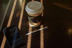 纸板杯用咖啡、热奶咖啡、拿铁、茶和智能手机在木桌上在咖啡馆在明亮的太阳发出光线 免版税库存图片