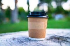 纸板站立在庭院里的咖啡杯 免版税库存照片