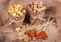 纸桶焦糖玉米花、烤花生在壳和棒棒糖 设置电影的膳食 图库摄影