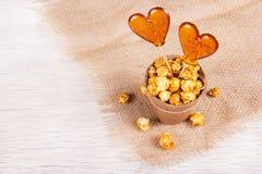 纸桶焦糖玉米花和两个糖果在一根棍子在白色木背景 以心脏的形式棒棒糖 免版税库存图片