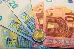 纸欧洲钞票和硬币 硬币是两欧元 库存图片