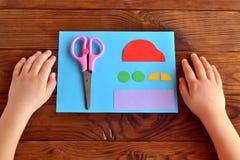 纸汽车和零件,剪刀 孩子在木桌上把他的手放 开玩笑艺术 免版税库存图片