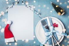 纸牌、白色板材和利器装饰了圣诞老人帽子和小杉树 设置顶视图的不可思议的圣诞节桌 复制空间 库存图片