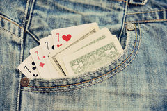 纸牌和金钱在蓝色牛仔裤装在口袋里 免版税图库摄影