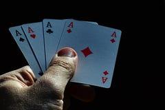从纸牌游戏说笑话者的四一点从法国甲板在黑暗的背景的男性左手举行了 免版税库存照片