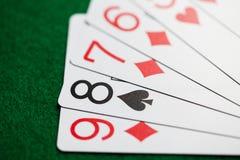 纸牌的纸牌游戏手在绿色赌博娱乐场布料的 库存图片