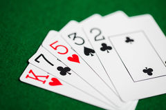 纸牌的纸牌游戏手在绿色赌博娱乐场布料的 免版税库存图片