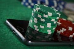 纸牌筹码和电话在桌上 免版税库存照片